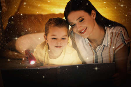 Mother with little child reading magic book at home Foto de archivo