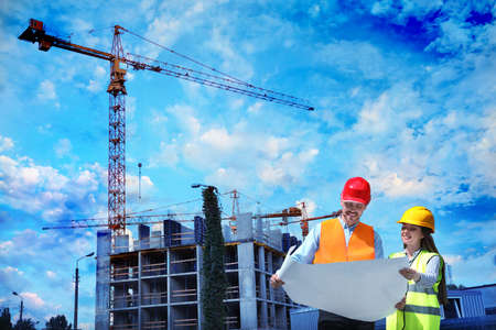 Professional engineers in safety equipment with drafting at construction site