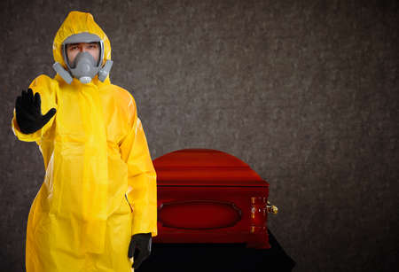Funeral during coronavirus pandemic. Man in protective suit near casket indoors