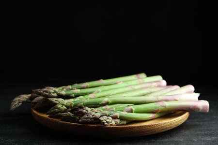 Fresh raw asparagus on black table, closeup. Space for text