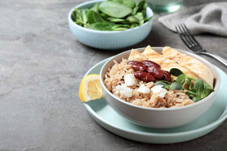 Tasty rice with beans and meat served on grey table