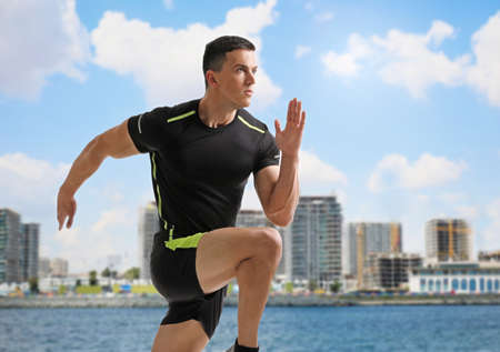 Athletic young man running near sea on sunny day Stockfoto