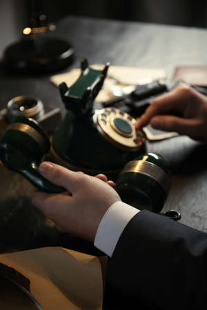 Detective dialing number on vintage telephone at table, closeup