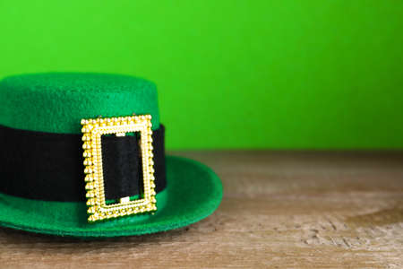 Green leprechaun hat on wooden table, space for text. St. Patrick's Day celebration