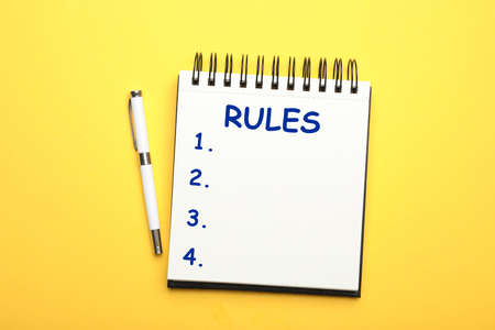 Notebook with list of rules and pen on yellow background, flat lay Stok Fotoğraf