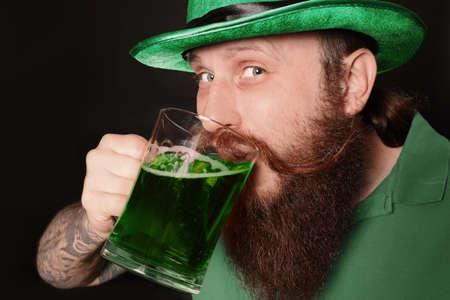 Bearded man drinking green beer on black background. St. Patrick's Day celebration Zdjęcie Seryjne