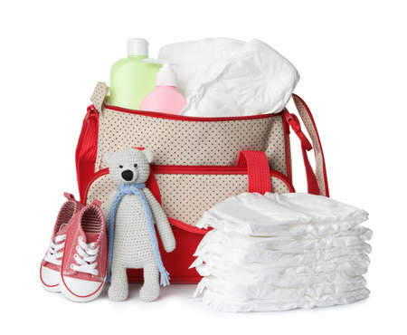 Maternity bag with disposable diapers and child's accessories on white background