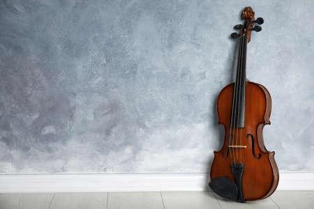 Classic violin on floor near grey wall. Space for text Standard-Bild