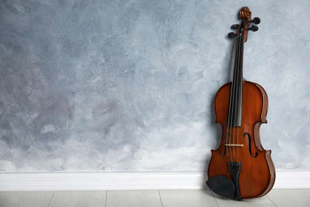 Classic violin on floor near grey wall. Space for text Stock Photo