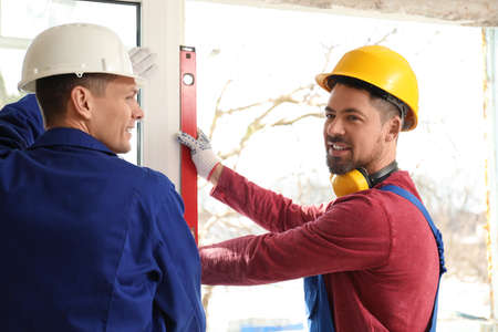 Workers using bubble level for installing window indoors