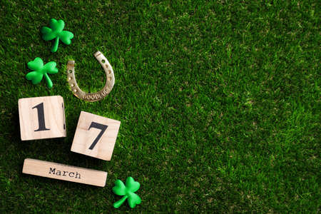 Flat lay composition with horseshoe and wooden block calendar on grass, space for text. St. Patrick's Day celebration