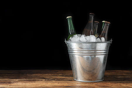 Metal bucket with bottles of beer and ice cubes on wooden table. Space for text