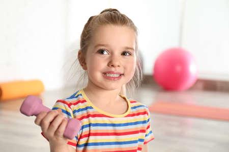 Little girl with dumbbell in hospital gym. Orthopedist's help