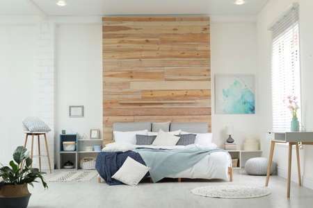 Stylish room interior with big comfortable bed