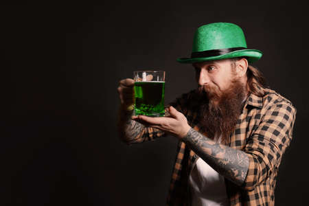 Bearded man with green beer on black background, space for text. St. Patrick's Day celebration Zdjęcie Seryjne