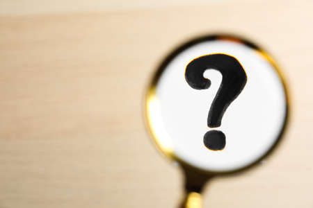 Question mark on beige background, view through magnifier glass. Space for text