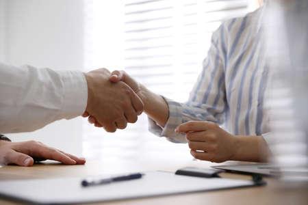 Business people shaking hands in office, closeup Foto de archivo