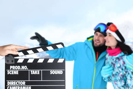 Assistant holding clapperboard and couple at mountain resort, closeup. Cinema production