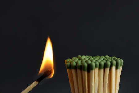 Burning match near unlit ones on dark background, closeup