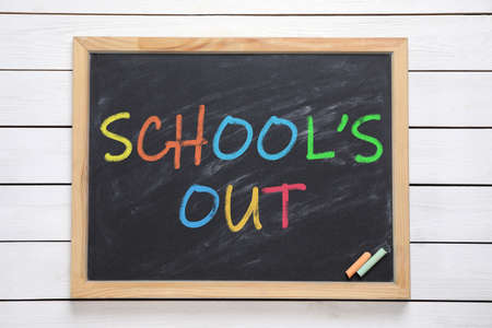 Chalkboard with text SCHOOL'S OUT on white wooden background, top view