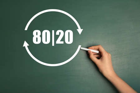 Pareto principle concept. Woman writing 80/20 on chalkboard, closeup Banque d'images