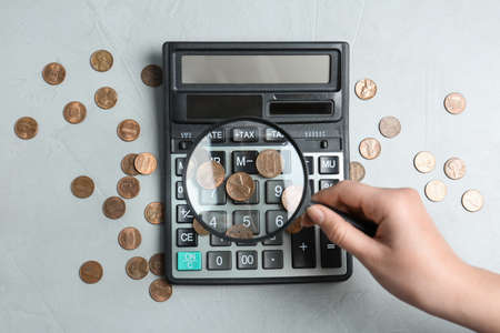 Woman looking through magnifying glass at calculator with coins on light grey table, flat lay. Search concept