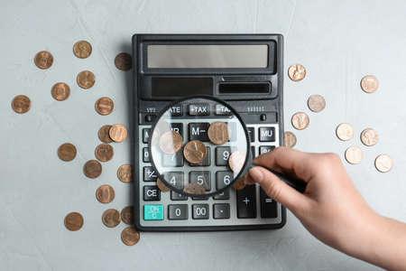Frau, die durch Lupe auf Taschenrechner mit Münzen auf hellgrauem Tisch schaut, flach. Suchkonzept