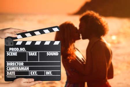 アシスタントはクラッパーボードを持ち、日没時にビーチでキスをする人々、クローズアップ。シネマプロダクション
