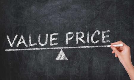 Woman writing phrase VALUE PRICE on blackboard, closeup