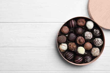 Box with tasty chocolate candies on white wooden table, flat lay. Space for text