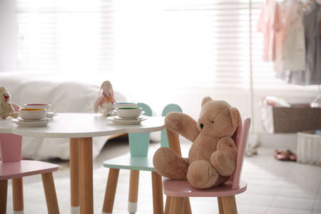Small table and chairs with bunny ears in children's room interior