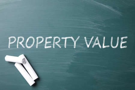 Pieces of white chalk and phrase PROPERTY VALUE on green chalkboard, flat lay 版權商用圖片