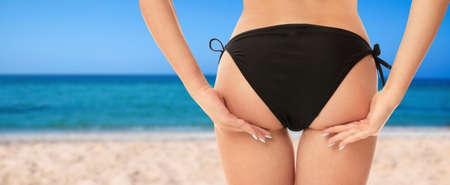 Sexy young woman wearing stylish bikini at beach on sunny day, closeup. Banner design