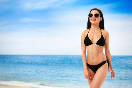 Pretty sexy woman with slim body in stylish black bikini near ocean on sunny day, space for text Фото со стока