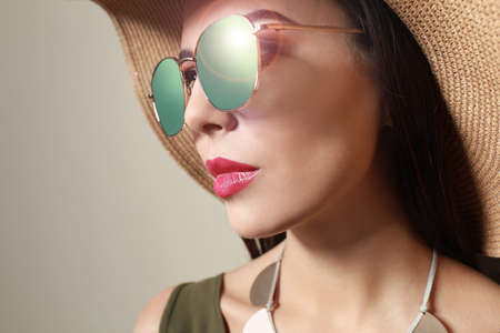 Beautiful woman in stylish sunglasses and hat on beige background