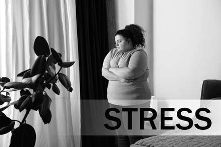 Overweight woman suffering from depression at home and word STRESS
