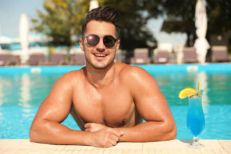 Young man with cocktail in pool on sunny day Фото со стока