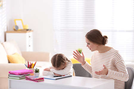 Mother scolding her daughter while helping with homework indoors Imagens