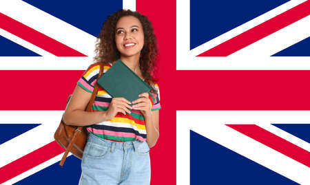 Beautiful African-American girl with book and flag of Great Britain as background. Learning English