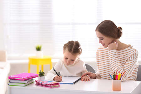 Woman helping her daughter with homework at table indoors