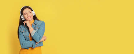 Young woman listening to music with headphones on yellow background, space for text. Banner design