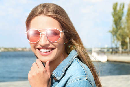 Young woman wearing stylish sunglasses near river