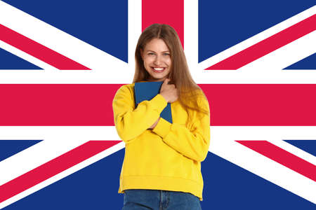 Beautiful young woman with book and flag of Great Britain as background. Learning English