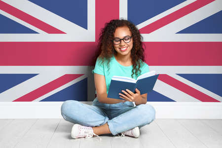 Beautiful young African-American girl reading book and flag of Great Britain on wall. Learning English