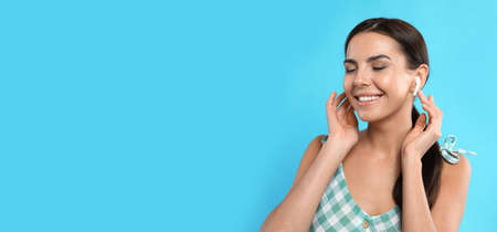 Young woman listening to music with wireless earphones on turquoise background, space for text. Banner design
