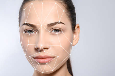 Facial recognition system. Woman with digital biometric grid on light background