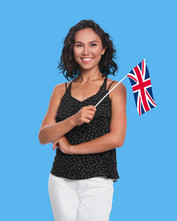 Happy young woman with flag of Great Britain on blue background. Learning English