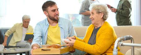Young man serving dinner for elderly woman in geriatric hospice, banner design. Senior people care Standard-Bild