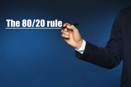 Pareto principle concept. Man writing 80/20 rule on blue background, closeup