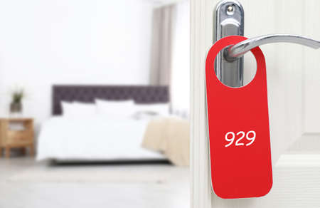 Open door with sign 929 on handle in hotel, closeup. Space for text
